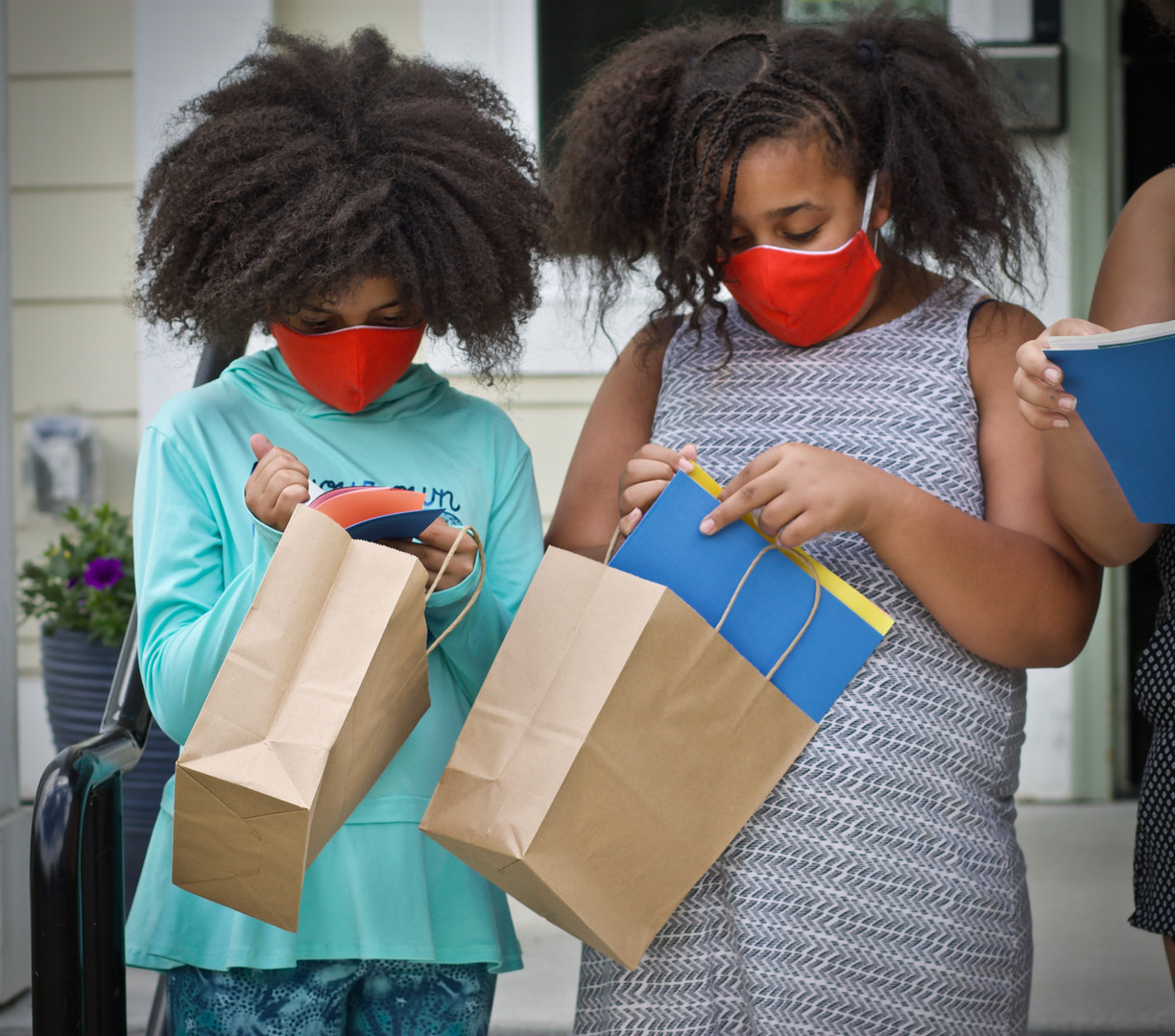 Girls in masks pick up their supply bags