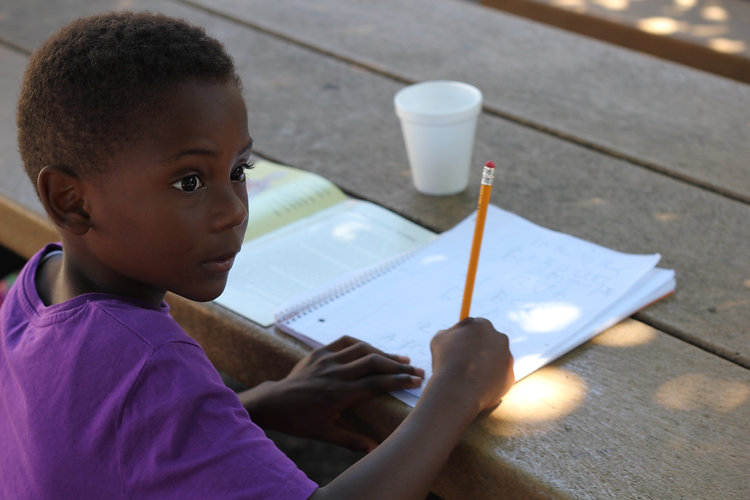 Little boy stares to the right with pencil and journal in hand