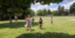 Kids run in a grassy park
