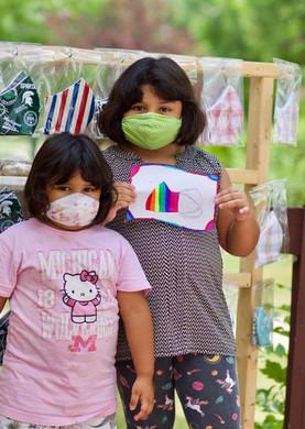 Girls in masks hold up flag design