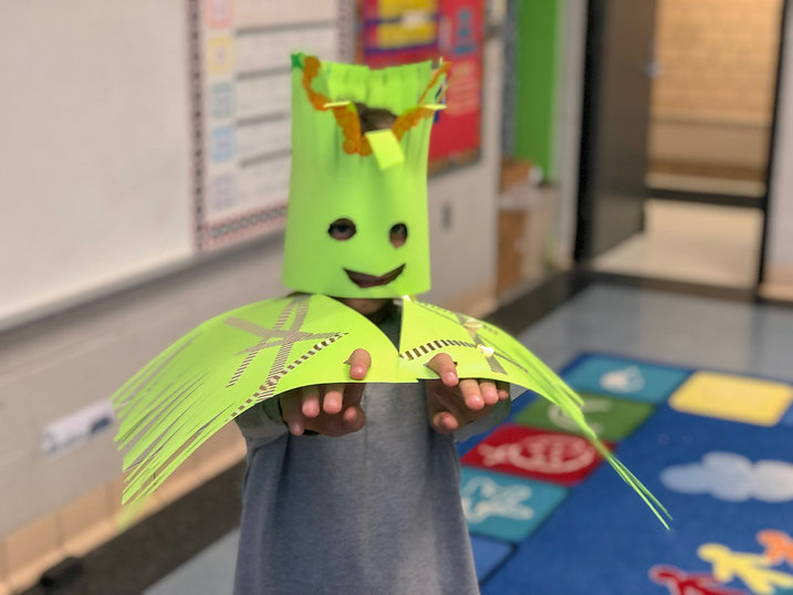 Child poses with bird costume he created with enrichment group