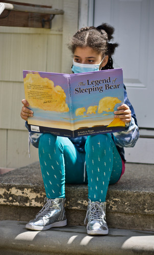 "Girl in mask reading ""The Legend of the Sleeping Bear"""