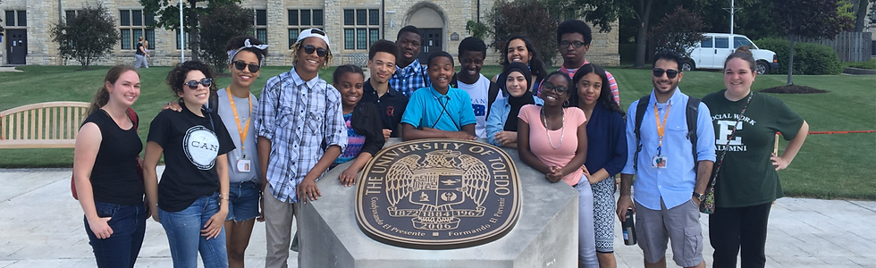 Teens pose around University of Toledo statue