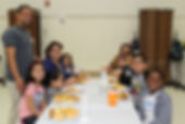 Families share a meal at a table together