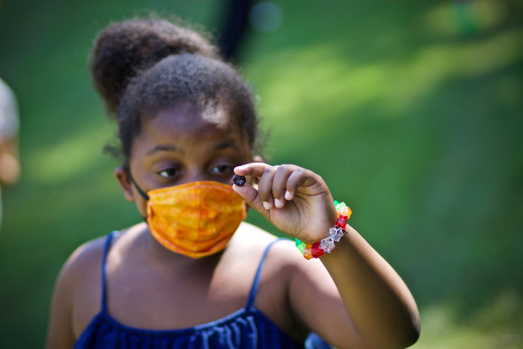 Girl with mask looks at berry she found