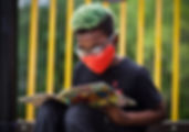 Boy with mask reads a book