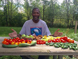 Smiling man seated at table of fresh vegetables