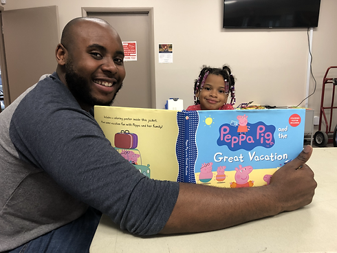 Mentor reads Peppa Pig to little girl