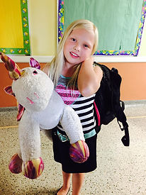 Girl shows off her backpack and a stuffed unicorn from back-to-school BBQ