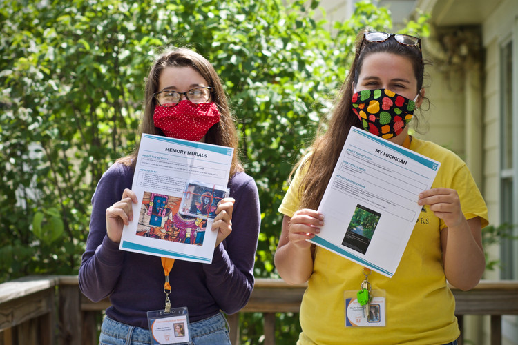 Team leaders with masks hold up lesson plans