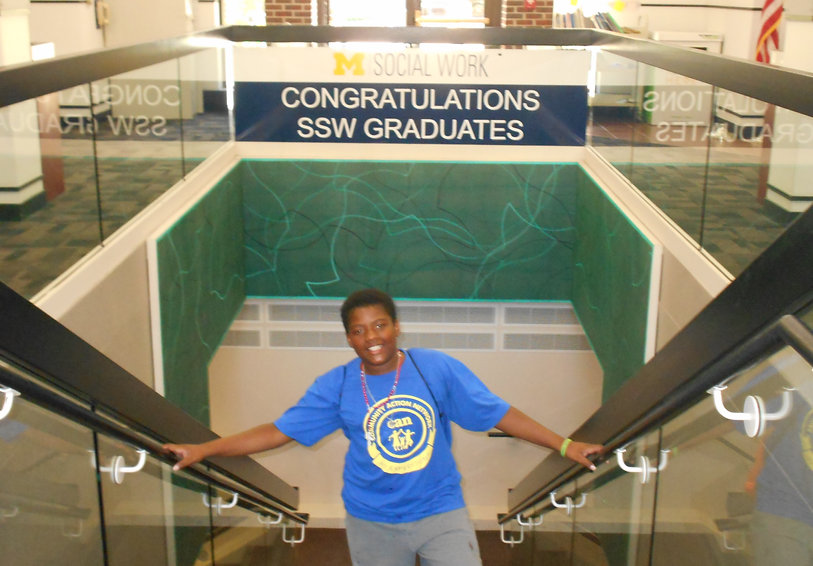 Teen poses on escalator in front of UM Social Work department sign