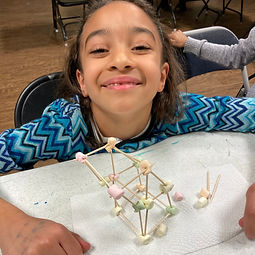 Girl smiles over marshmallow-toothpick structure