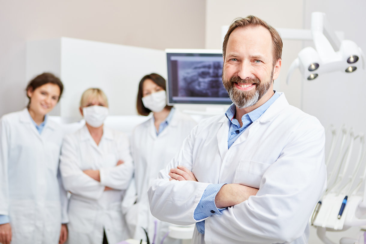 Smiling dentist with team to training in