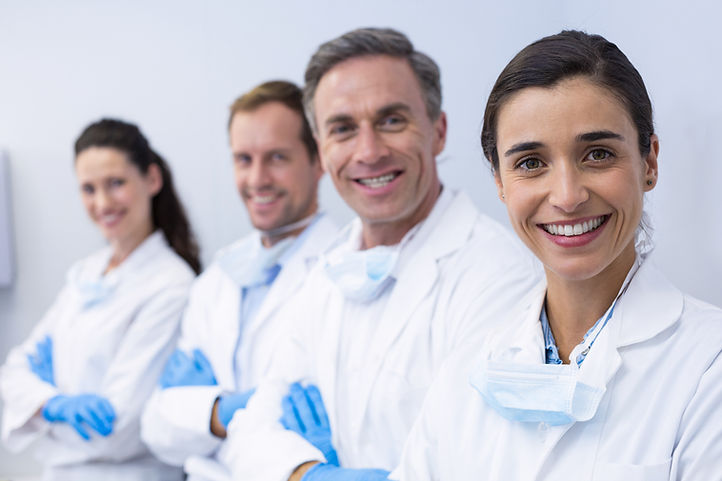 Portrait of smiling dentists standing wi
