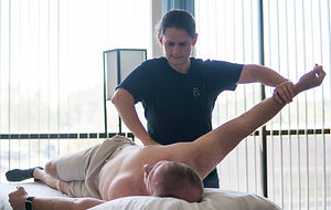 female massage and bodywork therapist opening a client's right side by pulling his right arm and pressing on exteranl obliques
