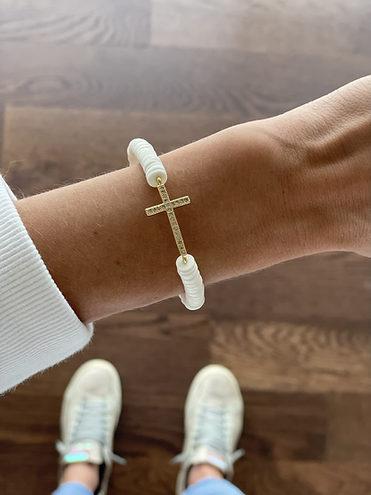 Gold cross on white clay