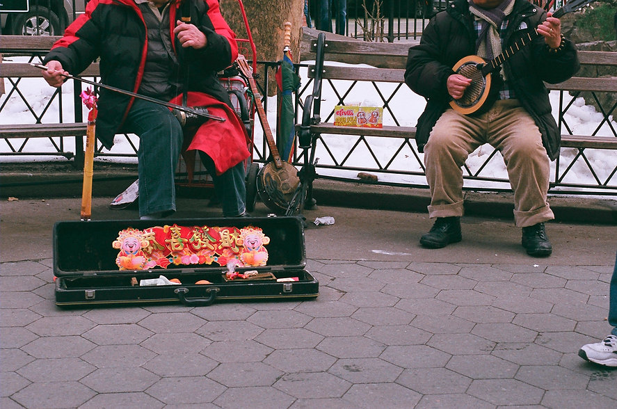 Yuqing Zhu film photography.  Street performers of traditional Chinese instruments (erhu) in Manhattan Chinatown.
