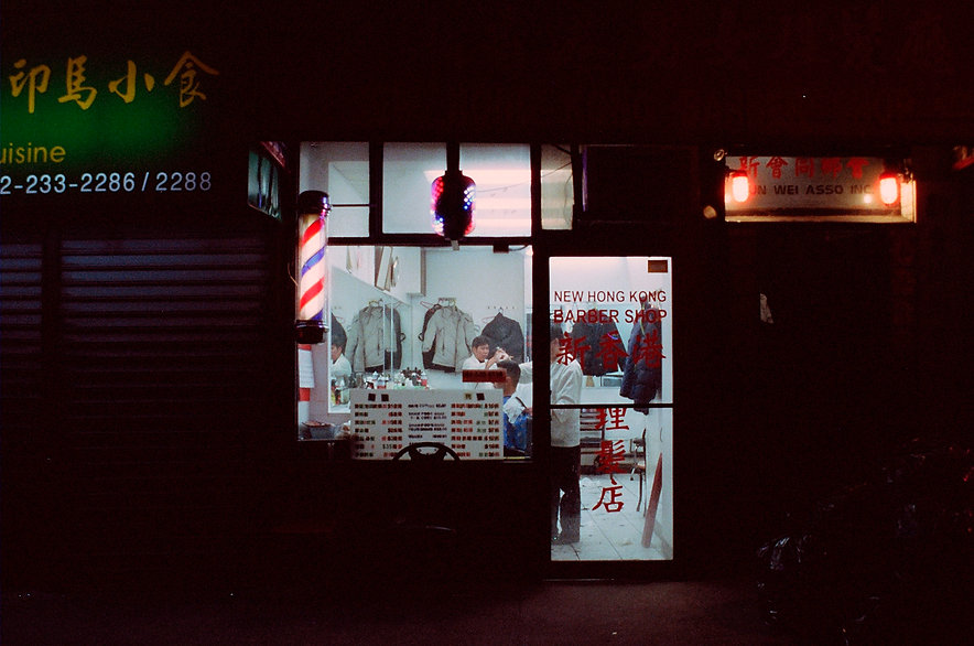 Yuqing Zhu film photography.  A barber in Manhattan Chinatown at night.