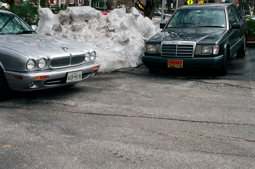 Yuqing Zhu film photography. Old cars in a parking lot with old snow.