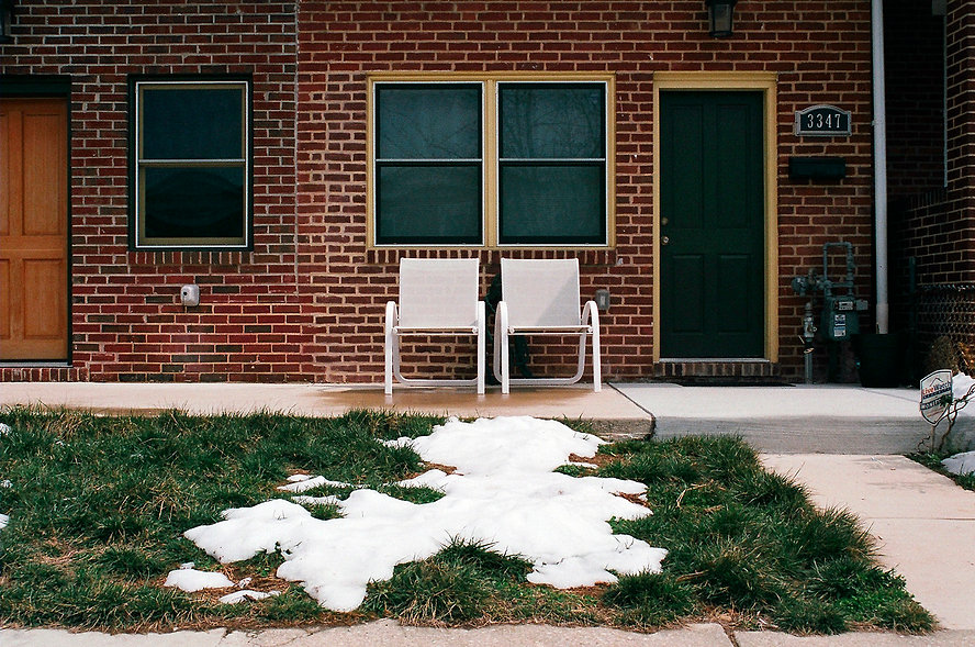 Yuqing Zhu film photography. A front lawn with white chairs and a patch of snow in Hampden, Baltimore.