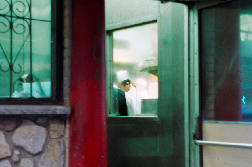 Yuqing Zhu film photography. Through the window into the kitchen of a Philadelphia Chinatown restaurant.