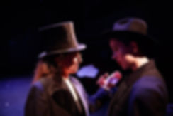 Production photo: two women in coats and top hats having a private conversation