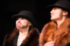 Production photo of two women dressed in fur-lined coats and top hats