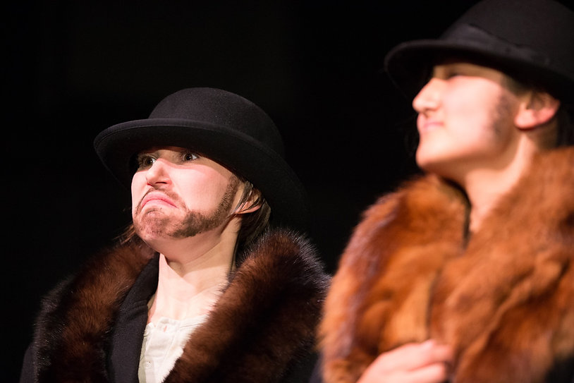 Production photo: two women dressed as men in fur-lied coats and top hats