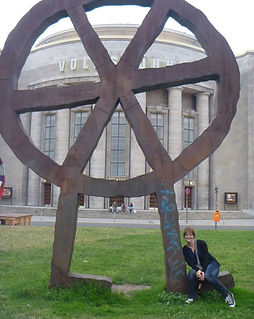 photo of Jessi posing next to a large metal sculpture in front of the Volksbühne in Berlin
