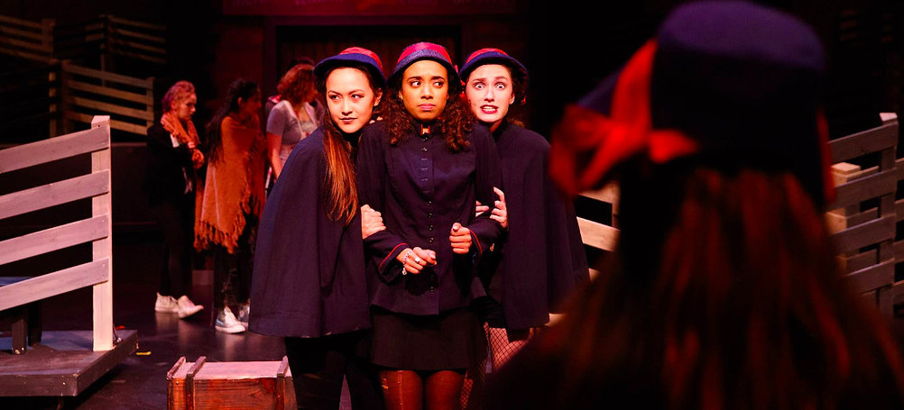Production photo: three women dressed as Salvation Army workers clasp each other, looking aound nervously