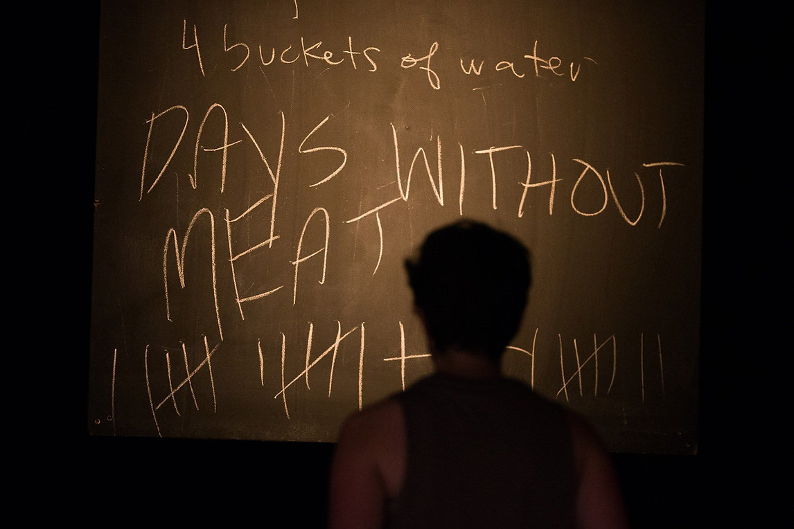 "Production photo: a silhoutte of a person facing a chalkboard that reads ""Days without meat"""