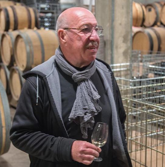 Le vigneron Pierre Fenals devant ses tonneaux un verre à la main