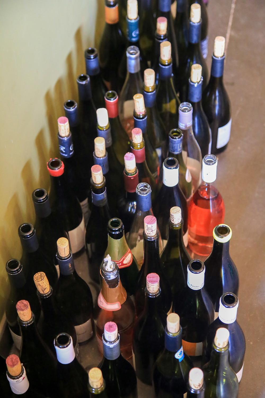Une trentaine de bouteilles de vin, vides, posées par terre