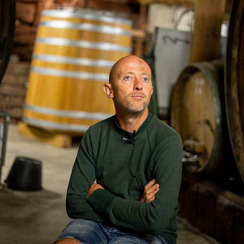 Le vigneron Christian Binner assis dans son chai bioclimatique, au milieu des foudres et tonneaux, en pull vert