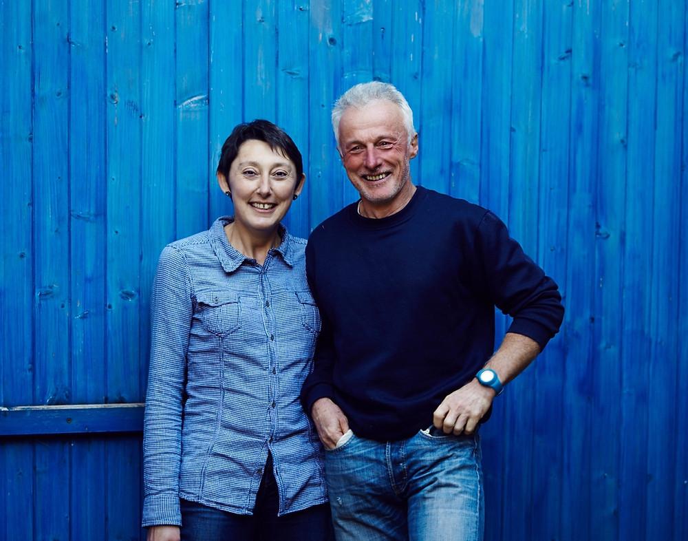 Le couple de vignerons de Moor debout devant un palissade bleue