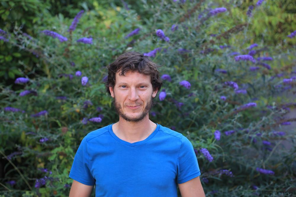 Matthieu Deiss, vigneron du domaine Marcel Deiss et du vignoble du rêveur en t-shirt bleu devant un arbuste