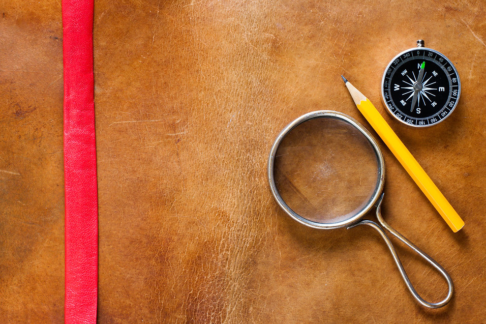 Magnifying glass, compass and pencil on