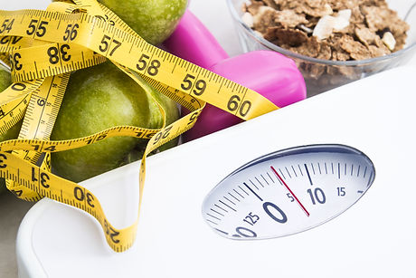 scale with cereals, fruit, weight and tape measure and concept of diet and healthy lifesty