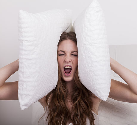 aggressive angry woman holds pillows to her ears due to extreme noise of the neighbours.jp