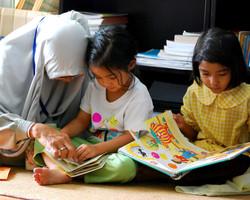 Muslim woman teaching kids