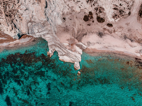 high-angle-aerial-view-of-a-beach-with-rocks-and-turquoise-sea.jpg