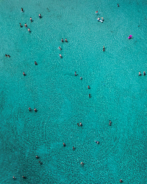 high-angle-aerial-view-of-people-swimming-in-turquoise-sea.jpg