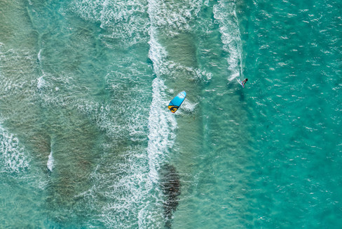 high-angle-aerial-view-of-a-kitesurfer-riding-through-the-waves-of-crystal-clear-sea.jpg