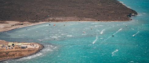 aerial-view-of-people-kitesurfing-and-windsurfing-on-ocean.jpg