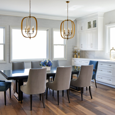 This sophisticated luxurious contemporary transitional dining area features custom-made adjustable maple wood table with brass finishes, velvet upholstery treatment chairs with detailed welts in contrast colors, grasscloth wallcovering, gold chandeliers and champagne architectural design details.
