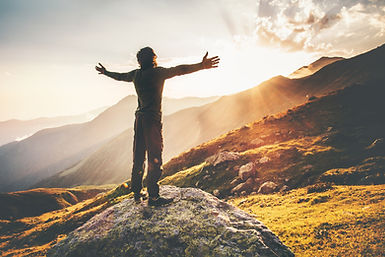 man standing in the sun on a mountain
