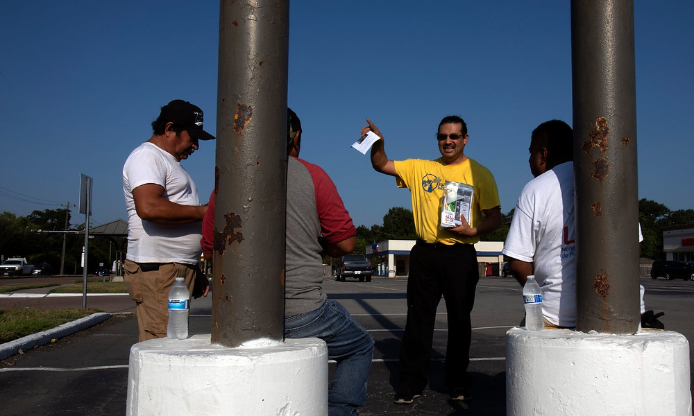 Alejandro Zuniga of the Fe y Justicia Worker Center offers water and literature to day laborers in Houston, where the Hurricane Harvey recovery has been marred by abuses of workers' rights. Photograph: Daniel Kramer
