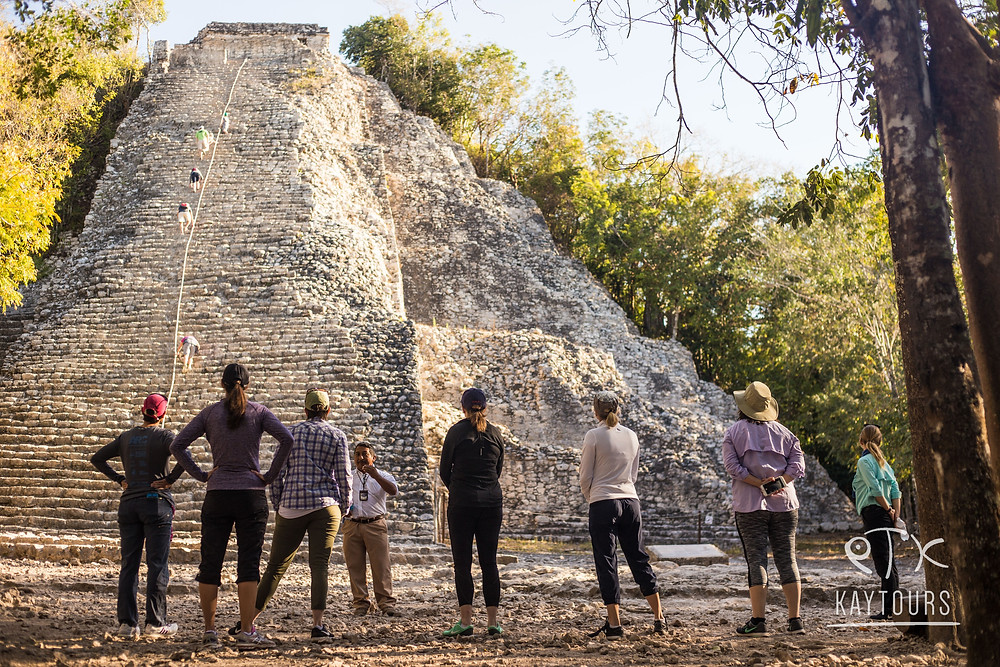 People standing at the bottom of the main structure in Coba Ruins ready to climb