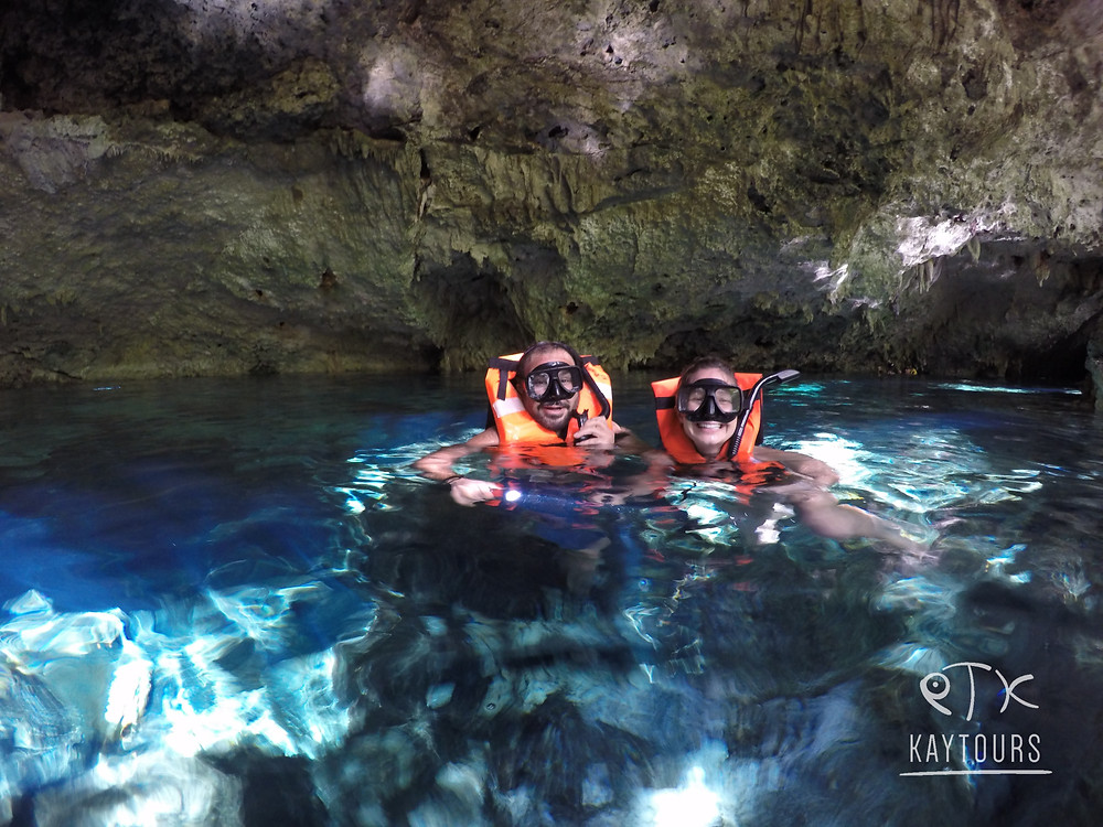 a man and a woman snorkeling in a cenote in the riviera maya