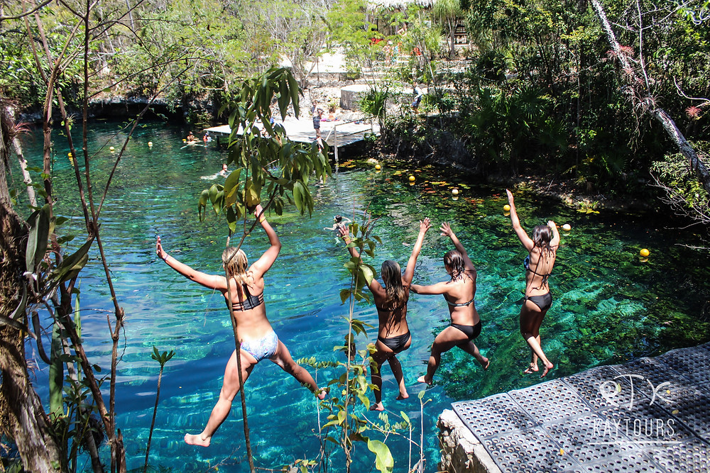 four women jumping in to a cenote in Mexico